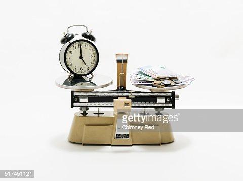 Clock & money balanced on industrial scales