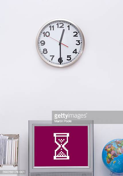 Clock on wall above computer monitor displaying hourglass icon