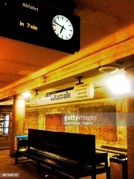 Clock Over Empty Bench At Illuminated Subway Station