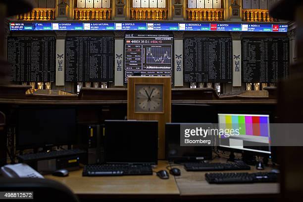 A clock sits on a desk as the Ibex 35 stock price information stands displayed on electronic screens inside the Madrid Stock Exchange also known as...