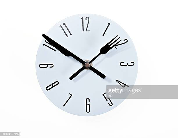 Clock with knife and fork on white