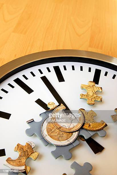 Clock with puzzle pieces showing eurocoins
