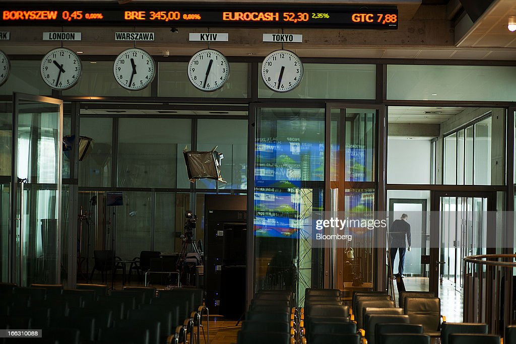 Clocks display world time zones beneath an electronic screen displaying financial data at the Warsaw Stock Exchange (WSE) in Warsaw, Poland, on Thursday, April 11, 2013. Poland's central bank kept interest rates unchanged at a record-low 3.25 percent yesterday. Photographer: Bartek Sadowski/Bloomerg
