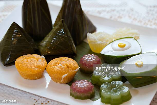 Clockwise from top steamed flour with coconut filling in tall pyramid banana leaf cassava cake tapioca with coconut cream in pandanus leaf Thai...