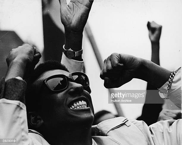 Cloeup of American Civil Rights leader Stokely Carmichael wearing sunglasses smiling and raising fists during a demonstration 1960s