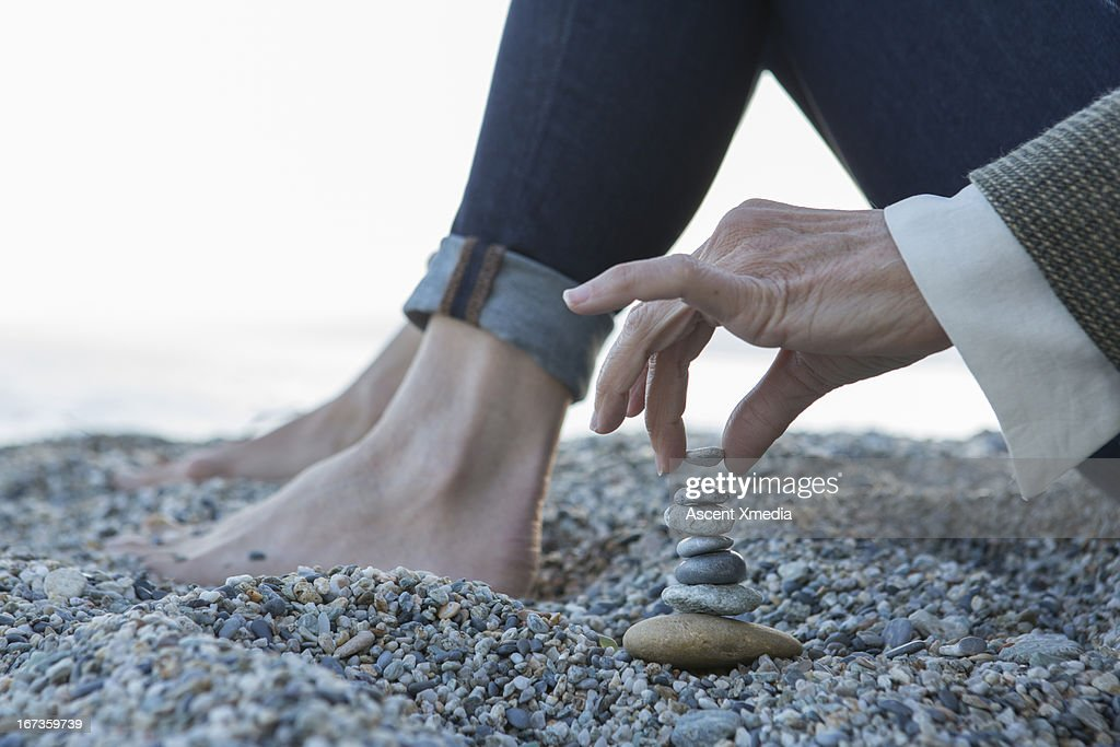 Cloe-up view of woman stacking pebbles, at beach : Stock Photo