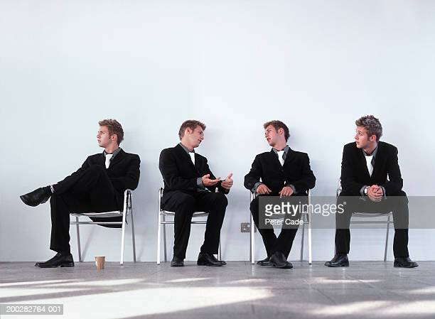 'Clones' of young businessman sitting on chairs (digital composite)