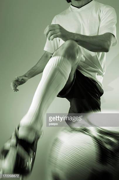 Close action shot of a soccer player kicking ball