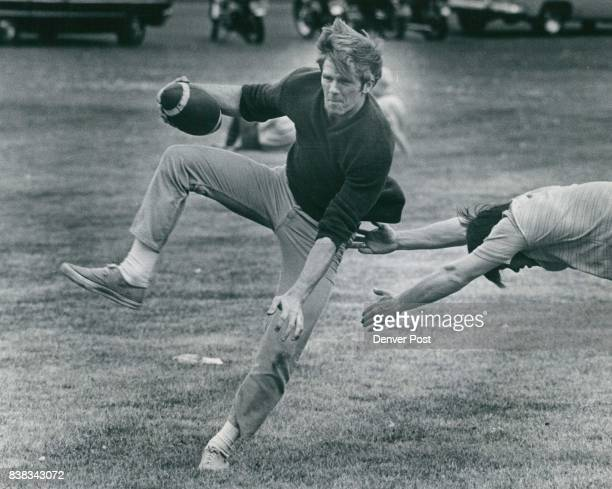 Close but No Touchdown Dennis Wineland of 2001 E 68tg Ave strains to avoid being touched in a touch football game by his brother Don 9031 Fir Drive...