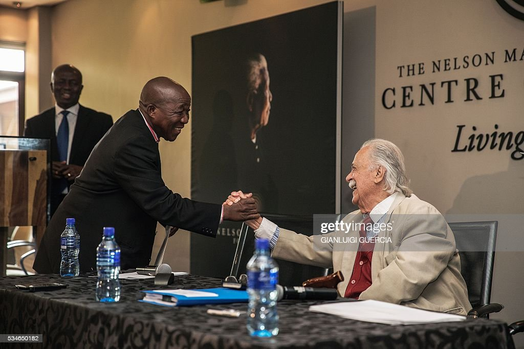 Close friend and legal advisor of the late South African President and global icon Nelson Mandela, George Bizos (R) congratulates Mandela's driver Michael Maponiya (L) during the public announcement of the distribution of all cash bequests made in terms of the Will of Nelson Mandela, at the Mandela Foundation in Johannesburg, on May 27, 2016. / AFP / GIANLUIGI