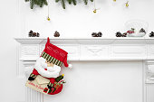 A close picture of beautifully decorated Santa Christmas socks with ho! ho! ho! word hanging on a fireplace waiting for presents