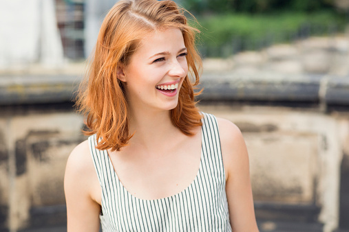 close portrait of a woman laughing outdoors
