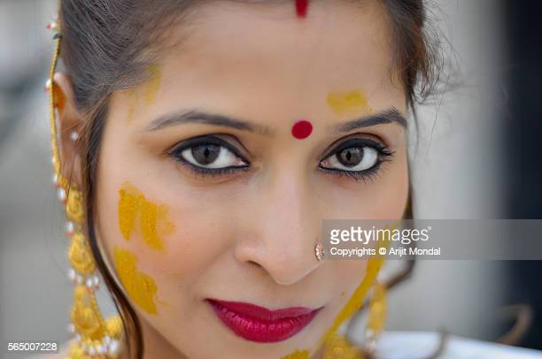 Close portrait of a young Indian woman with gold jewellery and Turmeric also called Haldi