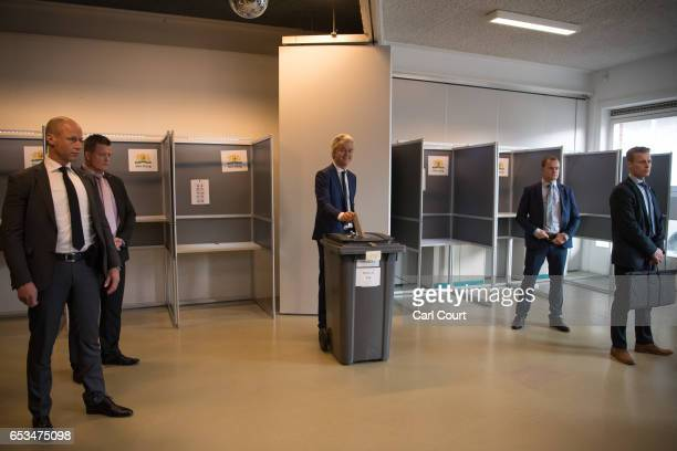 Close protection police officers surround Geert Wilders the leader of the rightwing Party for Freedom as he casts his vote during the Dutch general...