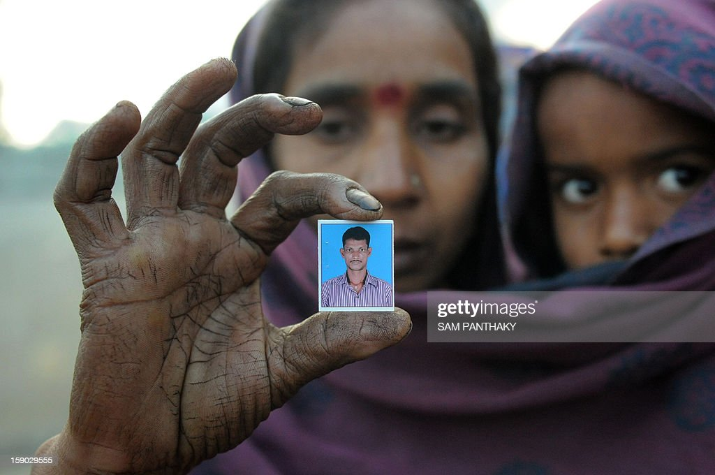 A close relative holds her child as she holds up a photograph of missing worker Rabi Swai outside the Indian Oil Corporation (IOC) plant at Hajira near Surat, some 275 kms from Ahmedabad on January 6, 2013. Three persons were killed in a major fire in a storage tank of IOC terminal, which was contained after a 21-hour operation by fire brigade team, officials said according to the Press Trust of India (PTI). AFP PHOTO / Sam PANTHAKY