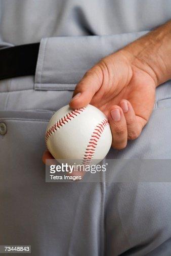 Close up baseball pitcher holding baseball behind back