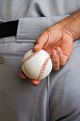 Close up baseball pitcher holding baseball behind back