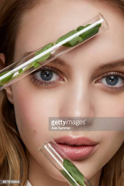 close up beauty shot of a woman with test tubes filled with green plants next to her face