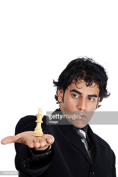 Close up business man holding a chess coin
