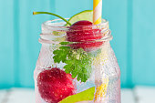 Close up cherry lemon soda or mojito in clear bottle glass in side view with copy space on blue wood background. Concept to present freshness and delicious beverage for summer party.