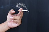 Close up cigarette or tobacco with smoke in hand and copy space'n