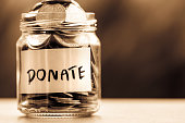Close up Coins in glass jar for giving and donation concept