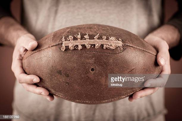Close Up Color Photo of Vintage Football Player Holding Ball
