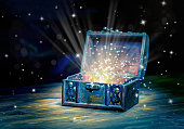 close up concept greeting card of opened vintage chest treasure with mystical miracle light on wooden background, beautiful fine art design