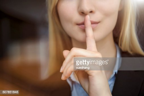 Close up cropped image of young businesswoman with finger on lips