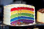 Close up color image depicting a cross section of a freshly baked and iced rainbow layer sponge cake on display at a food market. Room for copy space.
