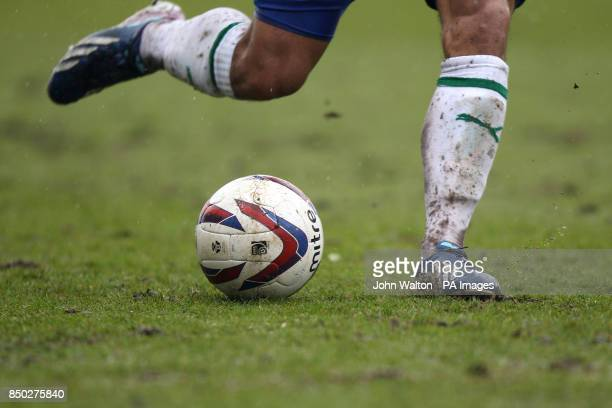 Close up detail of a players legs and football boots in the wet and mud