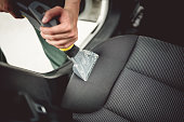 Close up details of worker vacuuming leather car interior