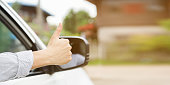 close up driver man hand showing thumb up through car's window for safety and assurance of driving concept.