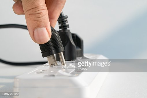 Close up Elderly hand plugging into electrical outlet : Stock Photo