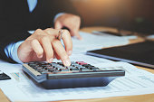 close up hand accountant using calculator with laptop. concept saving finance and accounting