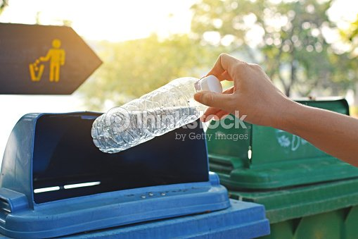 Close up hand holding empty bottle into the trash : Stock Photo