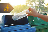 Close up hand holding empty bottle into the trash