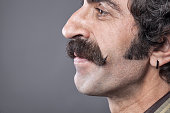 Close up photo of handlebar mustaches of smiling man on gray background.The model is on the right side of frame and faced to blank gray left side.Side view of model is seen.He is smiling.The hair colo