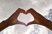Close up hands forming the heart and sky