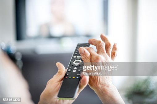 Close Up Hands Of Senior Woman Using TV Remote Control : Stock Photo