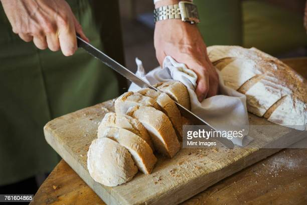Close up high angle view of person slicing freshly baked loaf of bread.