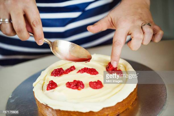 Close up high angle view of person wearing a blue and white stripy apron assembling a layer cake, holding spoon, placing raspberries on layer of cream.