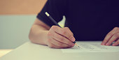 close up high school student man hand writing by marking choices on answer sheet paper for final examination test in classroom concept
