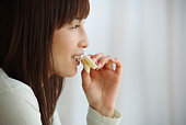 Close Up Image of a Woman Eating a Sandwich, Side View