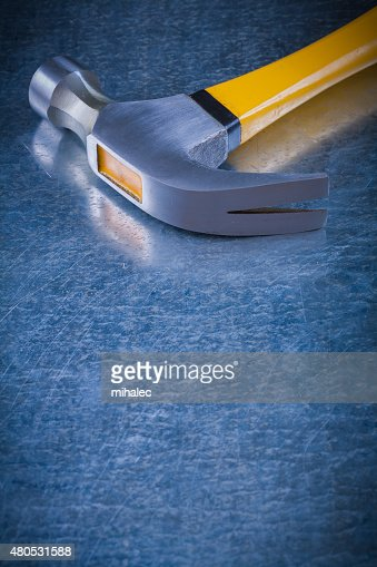 Close up image of claw hammer on scratched vintage metallic : Stock Photo