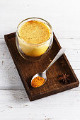 Close up image of golden latte in a wooden box over white wooden table