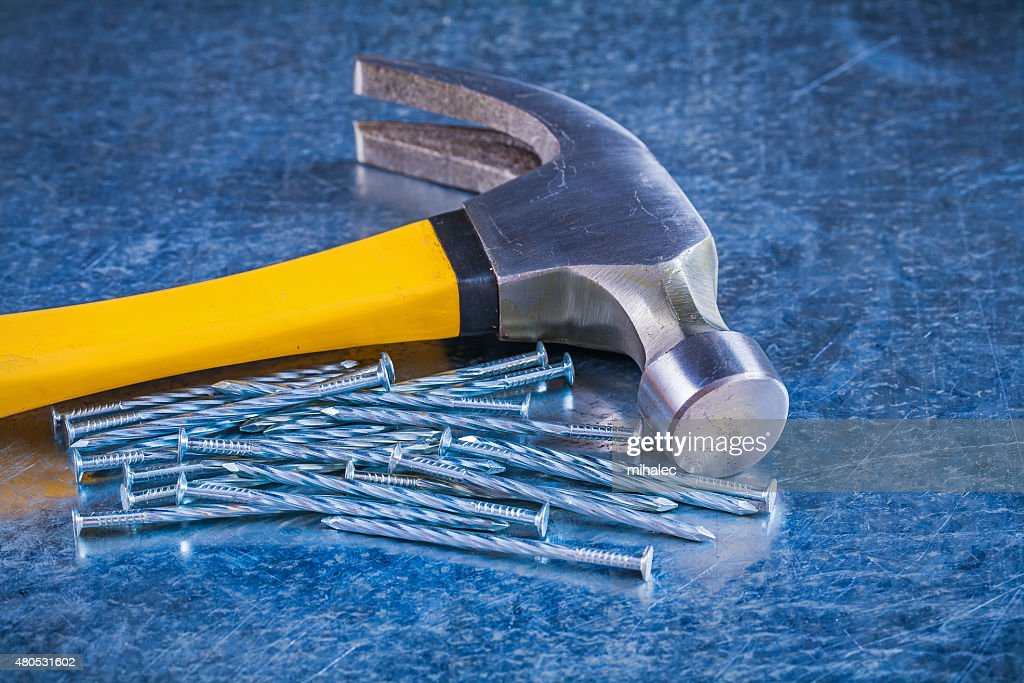 Close up image of metal construction nails with claw hammer : Bildbanksbilder