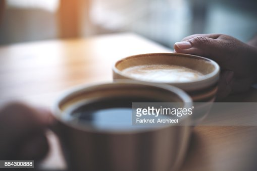 Close up image of two people clink coffee cups on wooden table in cafe : Stock Photo