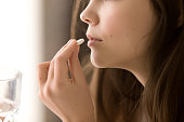 Close up image of woman putting white round pill in mouth. Sick female taking medicines, antidepressant, painkiller or antibiotic. Young lady drinking contraceptives. Pharmacy and healthcare concept