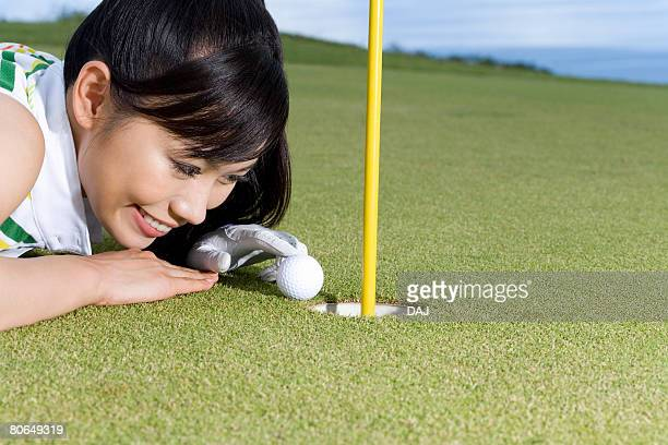 Close Up Image of Woman Touching Golf Ball by Cup